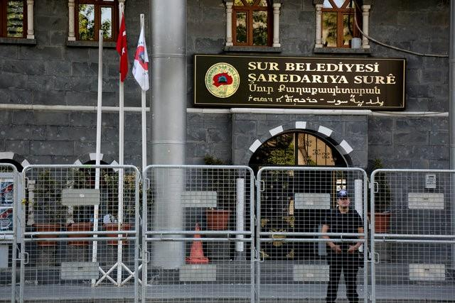 A riot police officer stands guard in front of Sur municipality office, following the removal of the local mayor from office after he was deemed to support Kurdish militants, in Diyarbakir