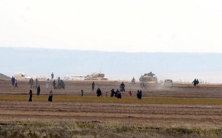 Syrian civilians, with Turkish Army tanks in the background, walk through the Turkish border as they are pictured from a village in Kilis province