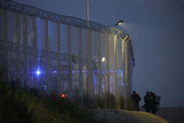 """French CRS riot police stand by the razor-wire topped fence which secures the road approach to the city and dissuades migrants from trying to reach Britain on lorries on the eve of the evacuation and dismantlement of the camp called the """"Jungle"""" in Calais"""