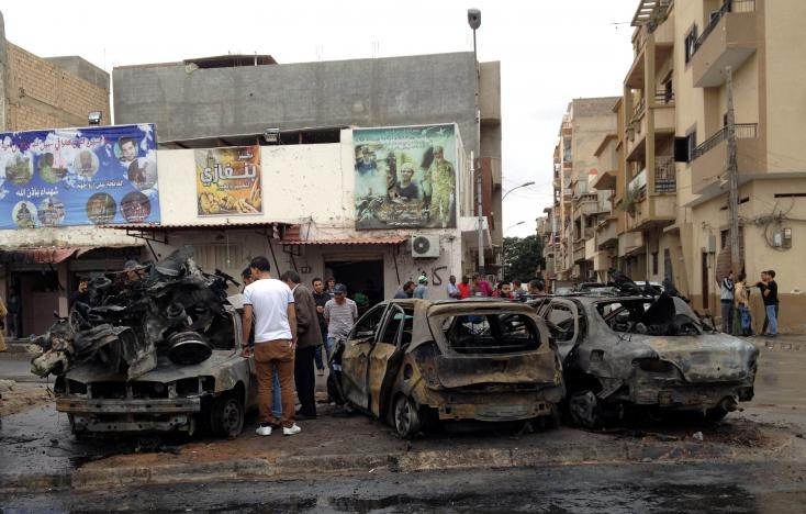 People look at the remnants of a car at the scene of a car bomb in Benghazi